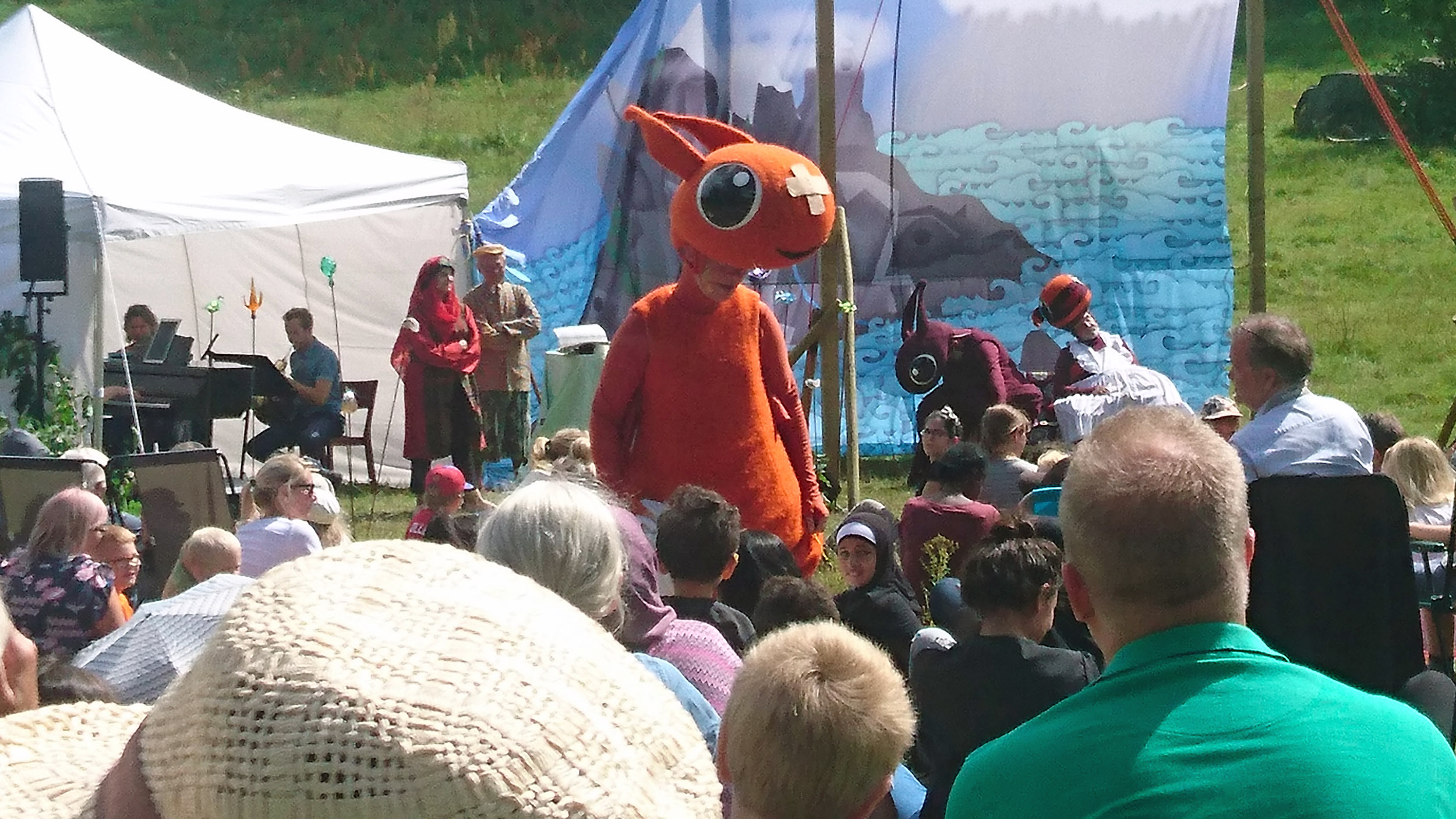 Draken Kjetil går ut och sjunger bland barnen i publiken.