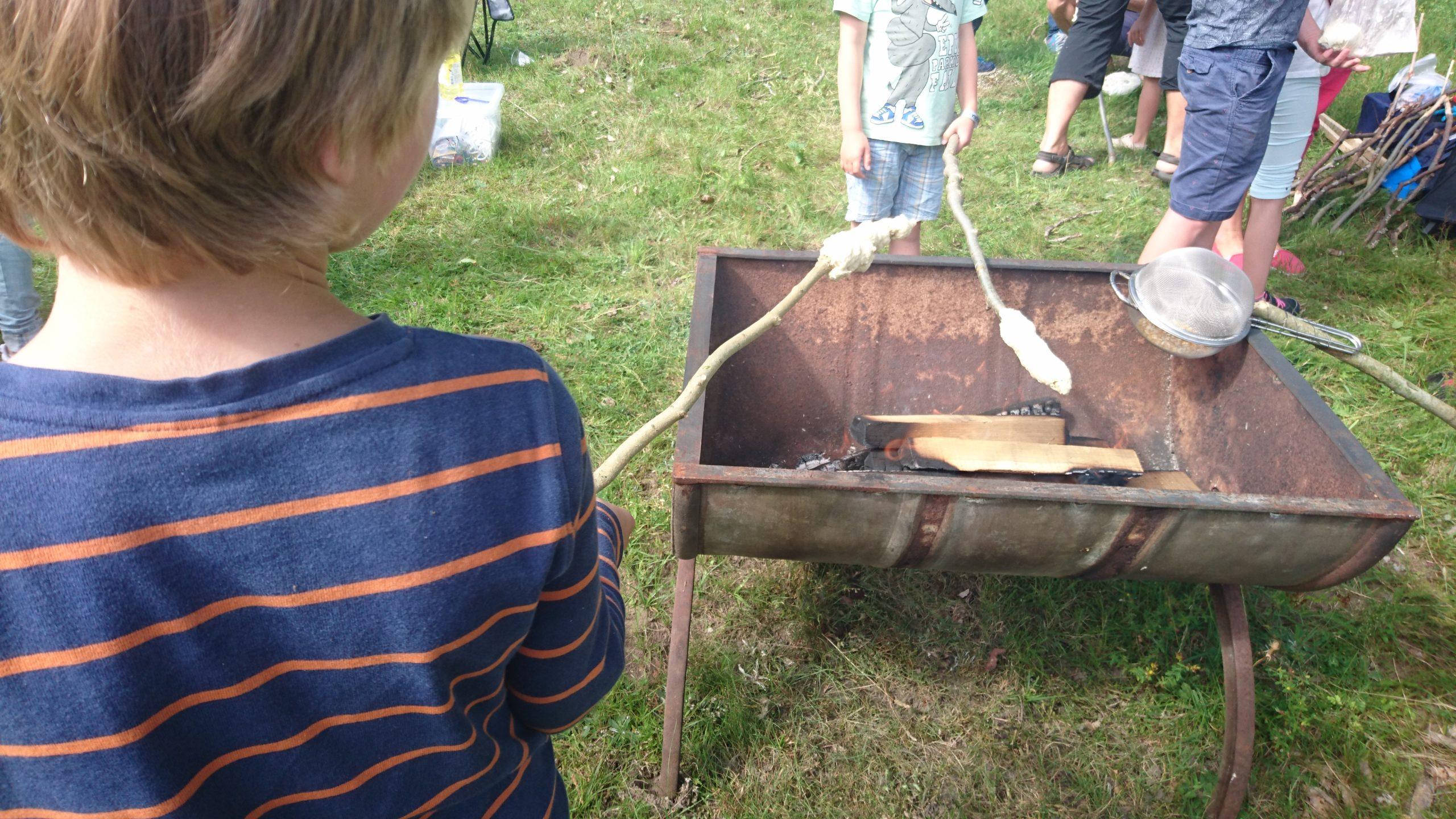 Brösarps scoutkår låter barnen baka pinnbröd.